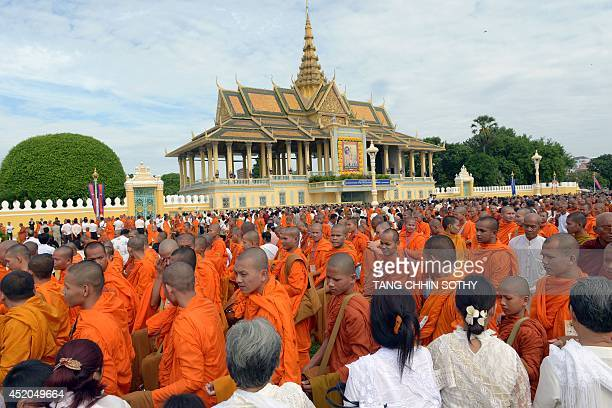Cambodian people offer food to Buddhist monks during a Buddhist ceremony in front of the Royal Palace in Phnom Penh on July 12 2014 In line with...