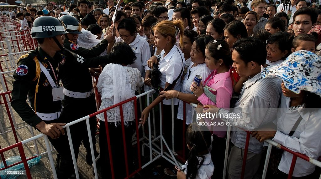 Cambodian people try to make their way through barriers secured by police officers as they come to pray and pay their respect for the late former king Norodom Sihanouk near the Royal Palace in Phnom Penh on February 3, 2013. Thousands of Cambodians have paid their last respects to their beloved former king Norodom Sihanouk as his body lay in state ahead of his cremation on February 4. AFP PHOTO/ Nicolas ASFOURI