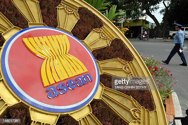 A Cambodian police officer walks past the ASEAN logo in front of the Peace Palace during the 45th Association of Southeast Asian Nations Foreign...