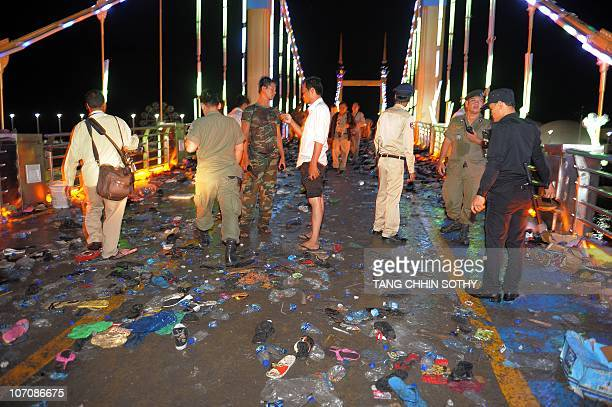 Cambodian police officials examine the bridge where at least 330 people died in a stampede in Phnom Penh on November 23 2010 while millions were out...