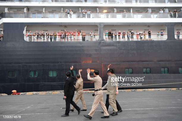 Cambodian police officials wave to passengers on board the Westerdam cruise ship in Sihanoukville on February 14 where the liner on February 13...