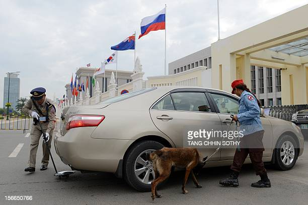 A Cambodian policeman checks under a car as a member of the Cambodian Mine Action Center leads a sniffer dog for a security check near the Peace...