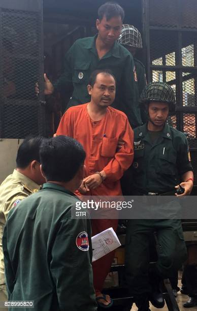 Cambodian political analyst Kim Sok is escorted by police upon his arrival at the Phnom Penh municipal court on August 10 2017 The Cambodian...