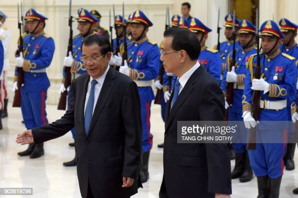 Cambodian Prime Minister Hun Sen and Chinese Premier Li Keqiang walk past the honour guard at the Peace Palace in Phnom Penh on January 11 2018 Li...