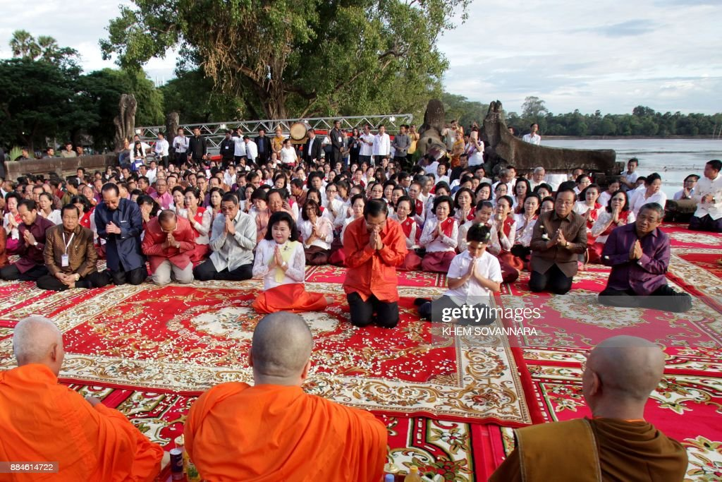Cambodian Prime Minister Hun Sen (middle C, in red) and his wife Bun Rany (middle L, in white top) offer prayers in front of Buddhist monks at the historic Angkor Wat temple in Siem Reap province on December 3, 2017. Thousands of orange-clad monks joined Cambodian Premier Hun Sen on December 3 for a prayer ceremony by the famed Angkor temple lauding 'political stability' after the main opposition party was dissolved, an act that has cemented the wily strongman's grip on power. /