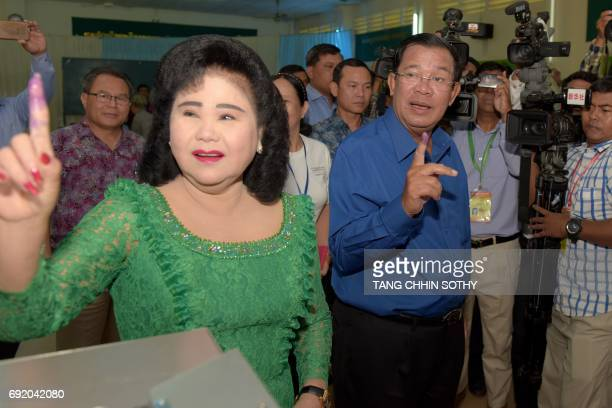 Cambodian Prime Minister Hun Sen and his wife Bun Rany show their inked fingers after casting their ballots at a polling station in Kandal province...