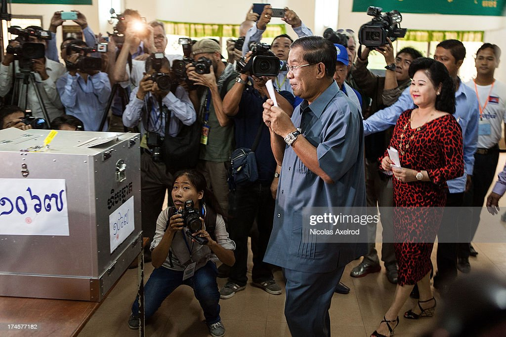 Cambodian Prime Minister Hun Sen casts his vote next to his wife Bun Rany (R) during the Cambodian general elections on July 28, 2013 in Phnom Penh, Cambodia. Cambodians go to the polls today in the fifth parliamentary election since 1993. 123 seats in the National Assembly are up for grabs to eight listed parties, with the main contenders being the ruling Cambodian Peoples Party (CPP) and the leading opposition Cambodia National Rescue Party (CNRP) led by Sam Rainsy.