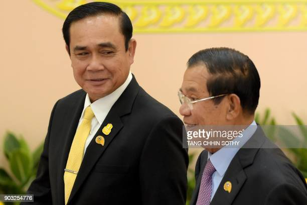 Cambodian Prime Minister Hun Sen walks with Thai Prime Minister Prayuth ChanOCha during the second MekongLancang Cooperation Leaders' Meeting at the...