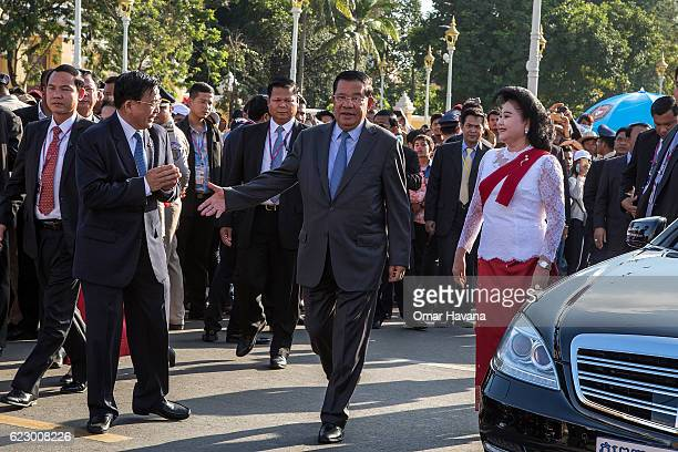Cambodian Prime Minister Samdech Hun Sen and First Lady Bun Rany greet authorities as they arrive at the Royal Pavilion on the Tonle Sap river during...