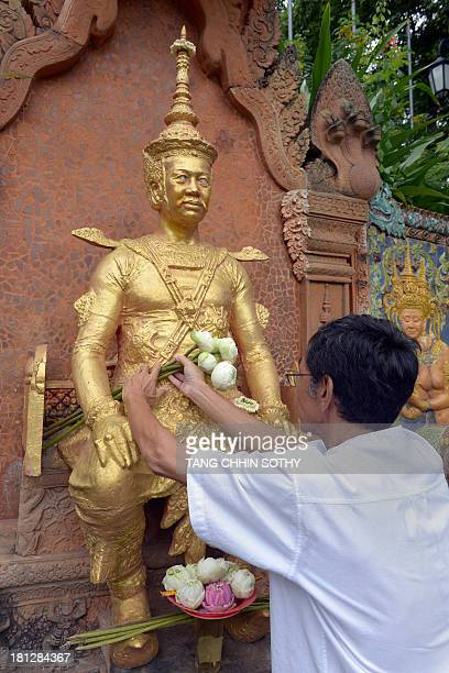 Cambodian Prince Sisowath Thomico lays flowers in front of a statue of King Sisowath during his hunger strike at Wat Phnom in Phnom Penh on September...