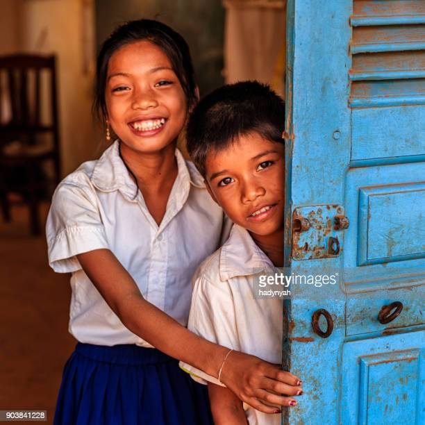 Cambodian school children standing in doorway of classroom, Cambodia