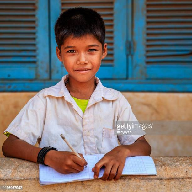 cambodian schoolboy doing homework near tonle sap, cambodia - traditionally cambodian stock pictures, royalty-free photos & images