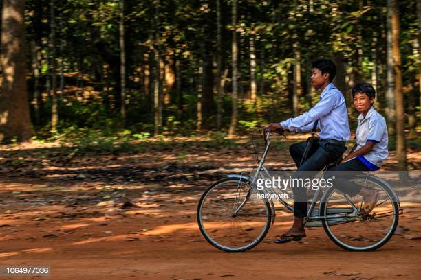 cambodian schoolboys riding bicycle, cambodia - traditionally cambodian stock pictures, royalty-free photos & images