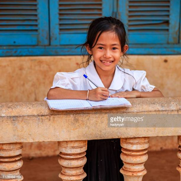 cambodian schoolgirl doing homework near tonle sap, cambodia - traditionally cambodian stock pictures, royalty-free photos & images