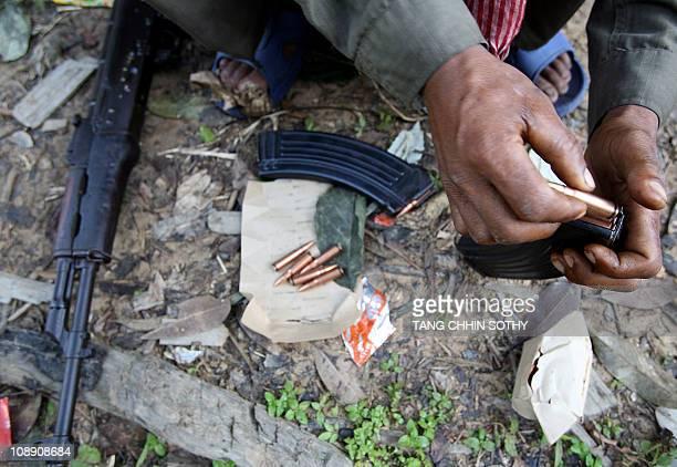 A Cambodian soldier loads bullets into a magazine of his AK47 at a jungle near the Preah Vihear temple in the Cambodian Preah Vihear province some...