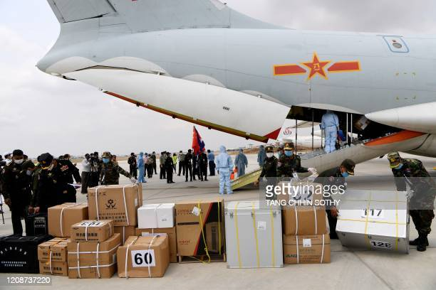Cambodian soldiers carry aid, to be used to combat the spread of the COVID-19 novel coronavirus, from a Chinese military plane at Phnom Penh...