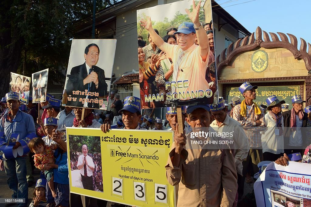 Cambodian supporters of Mam Sonando (C poster), owner of the independent Beehive radio station, display banners and placards in front of the Appeal court in Phnom Penh on March 5, 2013. A prominent critic of Cambodia's government, sentenced to 20 years in prison for an alleged secessionist plot, on March 5, pleaded not guilty during his appeal hearing.