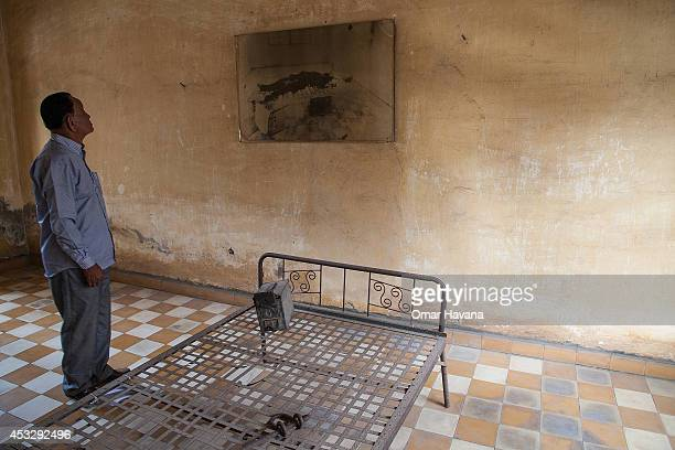 Cambodian survivor stands in one of the torture rooms of Tuol Sleng prison also known as S21 after the announcement of the verdict for former Khmer...