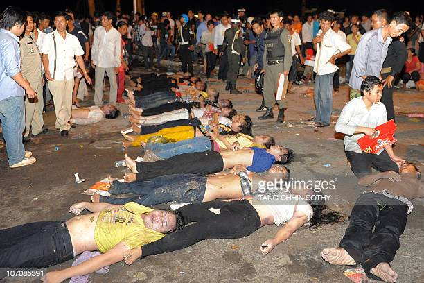 Cambodian tries to help an unconscious man near a bridge in Phnom Penh on November 23 2010 after at least 105 people died in a stampede while...