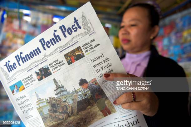 A Cambodian vendor reads the Phnom Penh Post newspaper at her newstand in Phnom Penh on May 7 2018 The newspaper hailed as Cambodia's last...