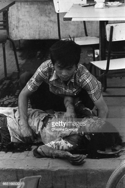 A Cambodian victim lies bleeding on the sidewalk after bombings by the Khmer Rouge in Phnom Penh