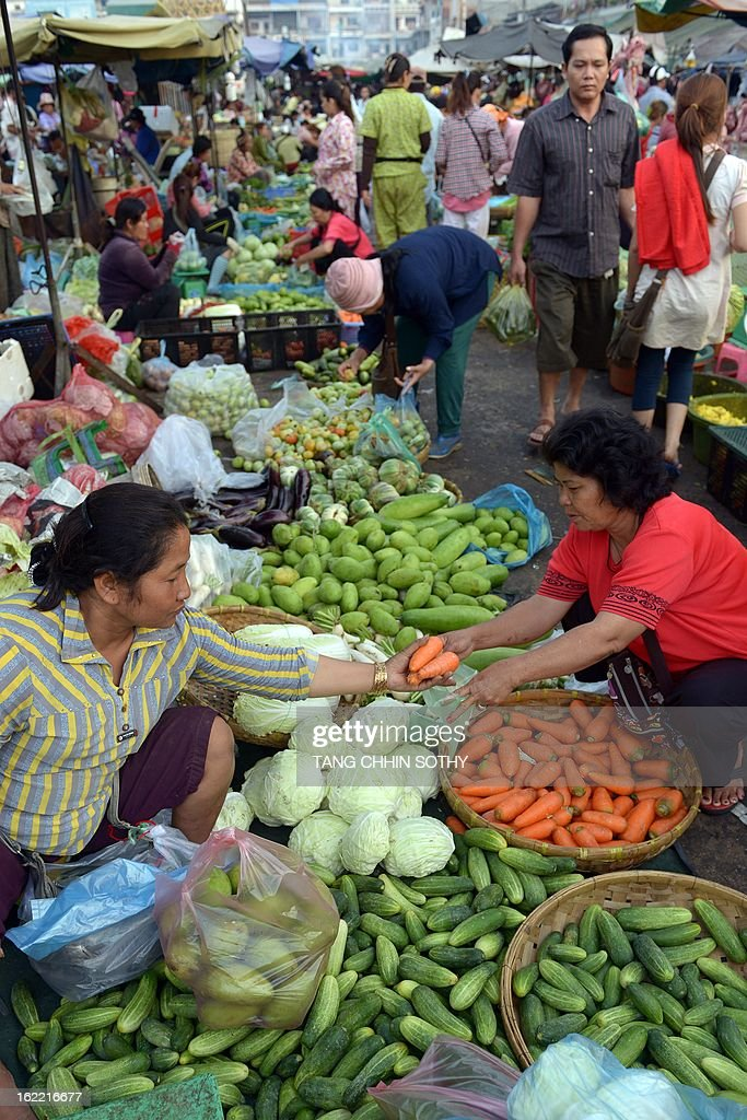 A Cambodian woman (R) buys vegetables at a market in Phnom Penh on February 21, 2013. Cambodia's economic growth accelerated to 7.3 percent last year thanks to buoyant activity in the agricultural, tourism, construction and garment sectors, Prime Minister Hun Sen said on February 20, 2013.