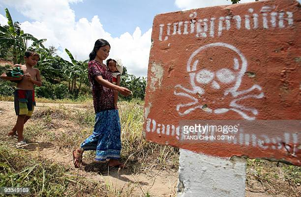 A Cambodian woman carrying a baby walks by landmine awareness sign at O'Chhoeu Kram village in the former Khmer Rouge's stronghold Pailin near the...