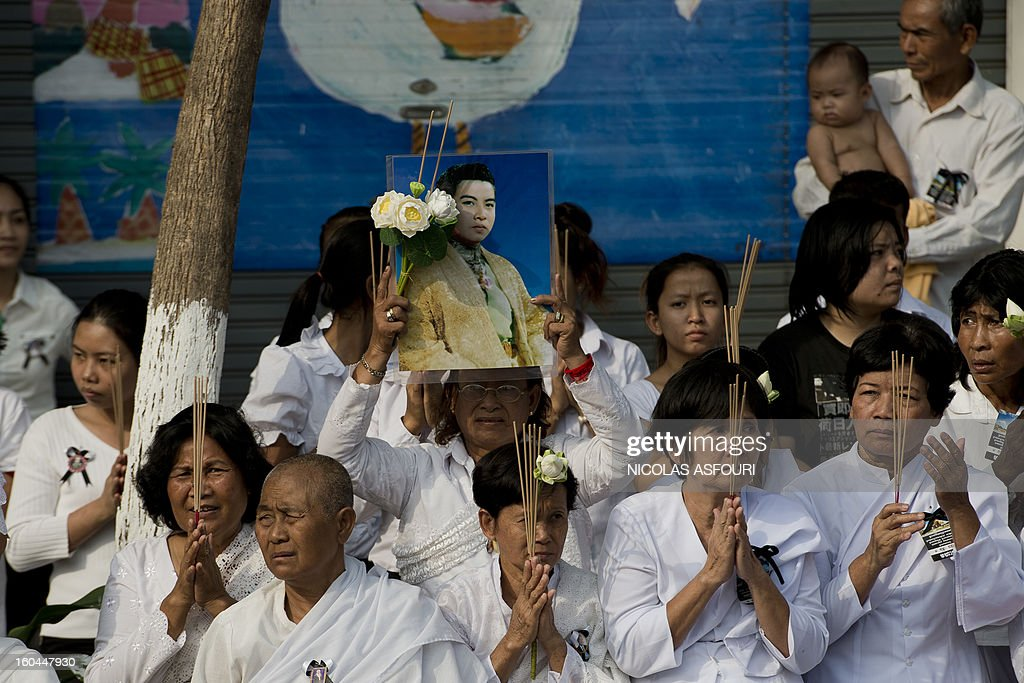 A Cambodian woman holds a photograph of the late former King Norodom Sihanouk as she look at his funeral procession near the the Royal Palace in Phnom Penh on February 1, 2013. Sihanouk, who abdicated in 2004 after steering Cambodia through six decades marked by independence from France, civil war, the murderous Khmer Rouge regime and finally peace, died of a heart attack in Beijing on October 15, 2012 and will be cremated on February 4. AFP PHOTO / Nicolas ASFOURI