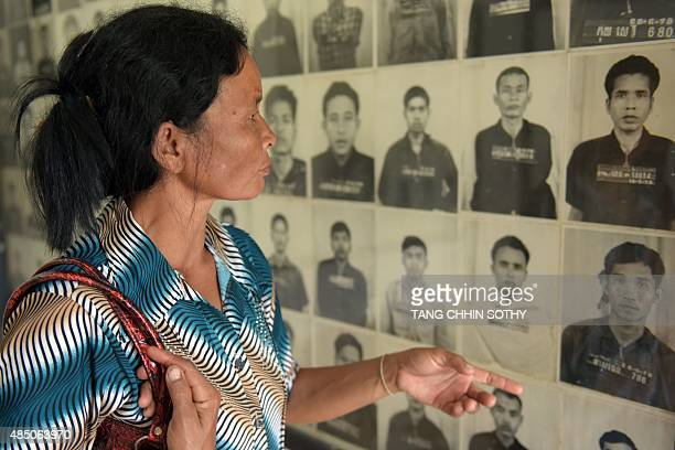 A Cambodian woman looks at portraits of victims of the Khmer Rouge displayed at the Tuol Sleng genocide museum in Phnom Penh on August 24 2015 The...