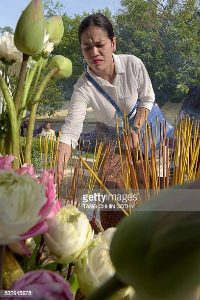 A Cambodian woman prays during the annual 'Day of Anger' at the Choeung Ek killing fields memorial in Phnom Penh on May 20 2016 More than 1000 people...