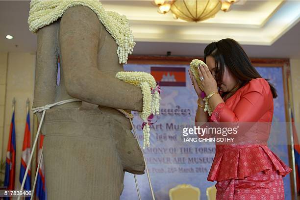 A Cambodian woman prays in front of a 10thcentury sandstone sculpture of the Hindu god Rama after it was returned from the Denver Art Museum in the...