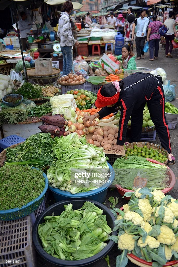 A Cambodian woman prepares vegetables at a market in Phnom Penh on January 18, 2013. The Association of Southeast Asian Nations (ASEAN), which comprises 10 countries, Brunei, Cambodia, Indonesia, Laos, Malaysia, Myanmar, Philippines, Singapore, Thailand and Vietnam have agreed that the Asean Economic Community (AEC) could be launched in 2015.