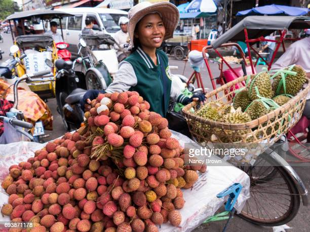 Cambodian Woman Selling Dragon and Durian Fruit in Phnom Penh Cambodia.