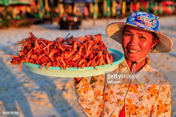 Cambodian woman selling fresh lobsters on the beach, Sihanoukville, Cambodia