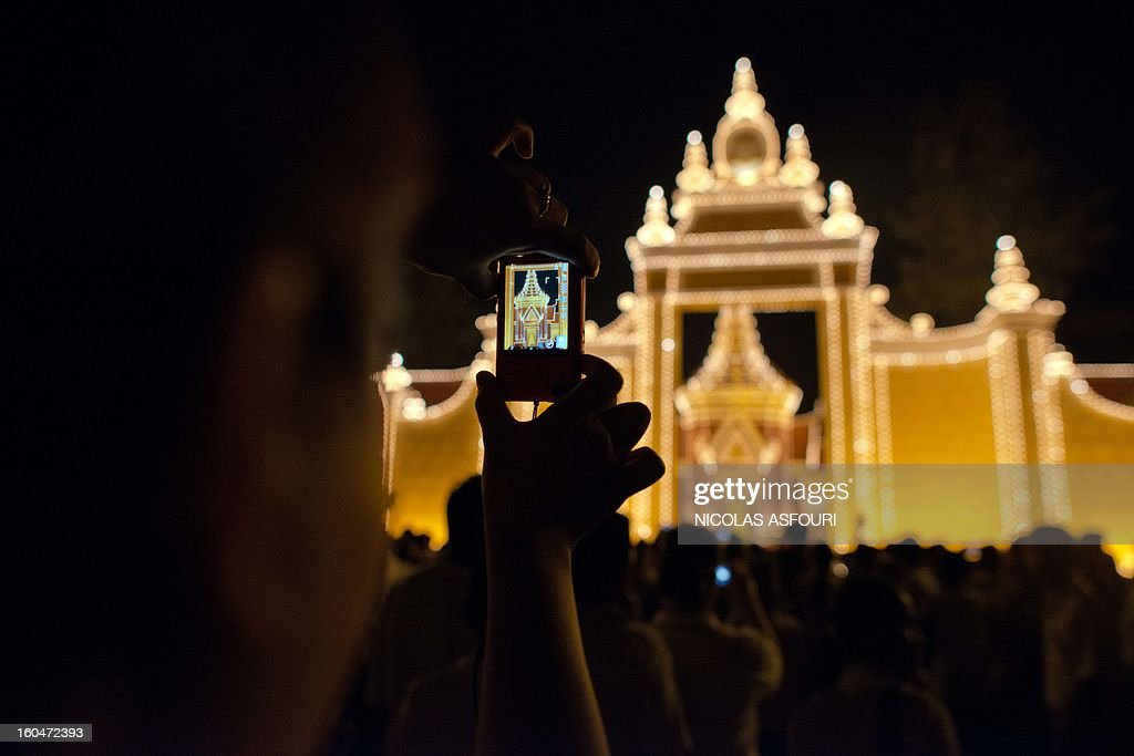 A Cambodian woman takes a photograph as mourners gather at a crematorium where a coffin bearing the remains of Cambodia's late King Norodom Sihanouk is placed, near the Royal Palace in Phnom Penh on February 1, 2013. Sihanouk, who abdicated in 2004 after steering Cambodia through six decades marked by independence from France, civil war, the murderous Khmer Rouge regime and finally peace, died of a heart attack in Beijing on October 15, 2012 and will be cremated on February 4. AFP PHOTO/ Nicolas ASFOURI