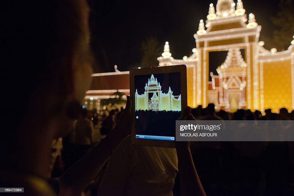A Cambodian woman takes a photograph with an iPad as mourners gather at a crematorium where a coffin bearing the remains of Cambodia's late King Norodom Sihanouk is placed, near the Royal Palace in Phnom Penh on February 1, 2013. Sihanouk, who abdicated in 2004 after steering Cambodia through six decades marked by independence from France, civil war, the murderous Khmer Rouge regime and finally peace, died of a heart attack in Beijing on October 15, 2012 and will be cremated on February 4. AFP PHOTO/ Nicolas ASFOURI