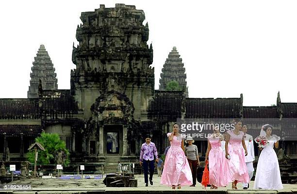 Cambodian women dressed in European style wedding dresses walk away from the ancient temple of Angkor Wat 02 May 2001 a site which attracts...
