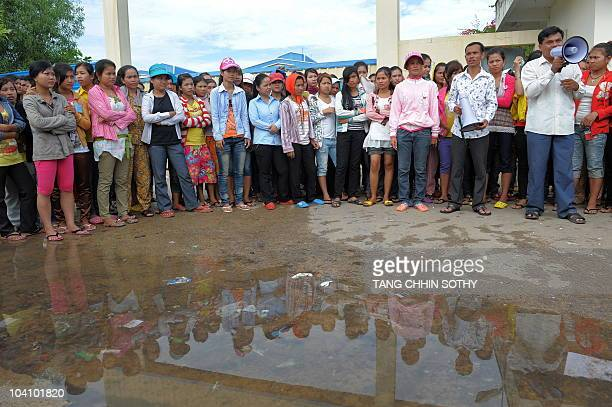 Cambodian workers stand and listen to a speech during a strike outside a garment factory in Phnom Penh on September 15, 2010.Tens of thousands of...
