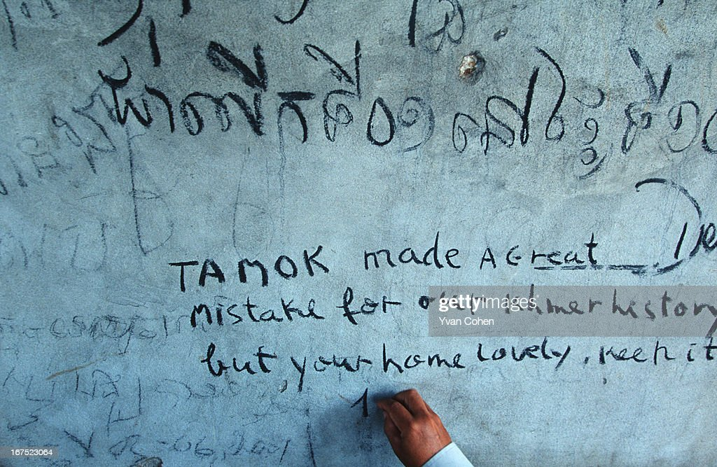 Cambodian writes graffiti on the wall of Ta Mok's abandoned house in Anlong Veng Province Cambodia ..