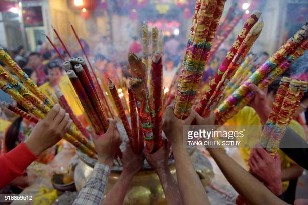 TOPSHOT CambodianChinese place various sizes of incense sticks into an urn at a temple to mark the start of the Lunar New Year in Kandal on February...