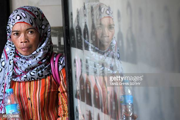 A CambodianMuslim looks at portrait photos of the victims of Khmer Rouge displayed for visitors at the Tuol Sleng genocide museum in Phnom Penh on...