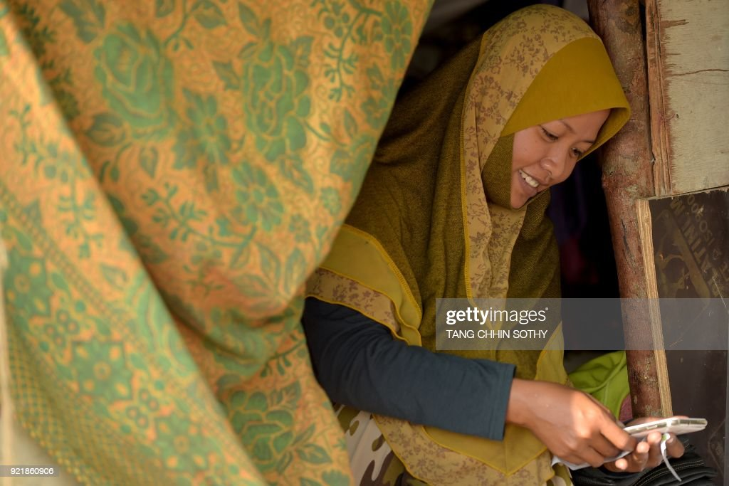 A Cambodian-Muslim woman checks her smartphone at her shelter along the Mekong river in Phnom Penh on February 21, 2018. /