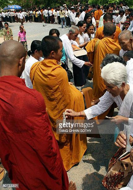 Cambodians offer food to Buddhist monks outside the Choeung Ek killing fields memorial in Phnom Penh on April 17, 2008. Cambodian people led by...
