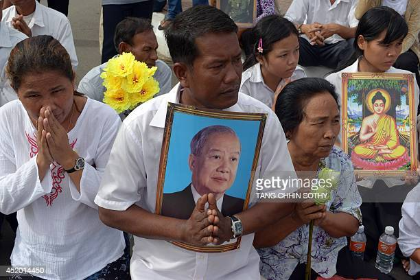 Cambodians pray during a procession of the remains of the late former king Norodom Sihanouk in front of the Royal Palace in Phnom Penh on July 11...