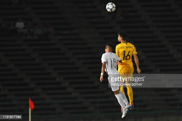 Cambodia's Brak Thiva fights for the ball with Australia's John Koutroumbis during the Tokyo 2020 Olympic Games men's Asian qualifier football match...