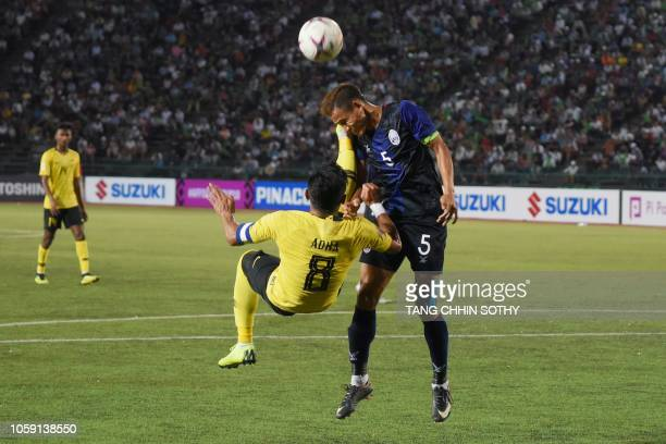 Cambodia's defender Soeuy Visal fights for the ball with Malaysia's forward Mohamad Zaquan Adha Abd Radzak during the AFF Suzuki Cup 2018 football...