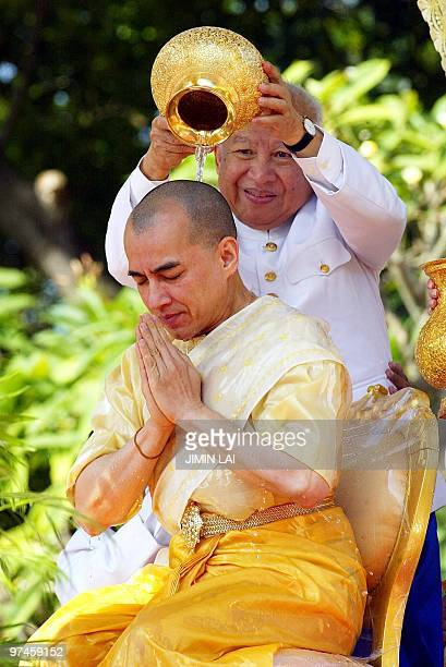 Cambodia's former King Norodom Sihanouk pours holy water on to his son new King Norodom Sihamoni during a religious ceremony at the Royal Palace in...