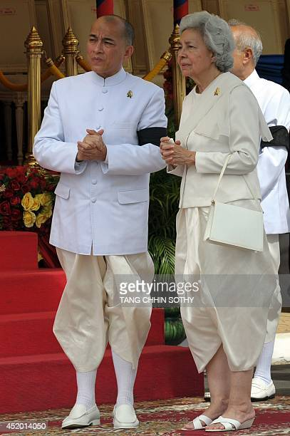 Cambodia's King Norodom Sihamoni and his mother former queen Monineath stand during a procession of the remains of the late former king Norodom...