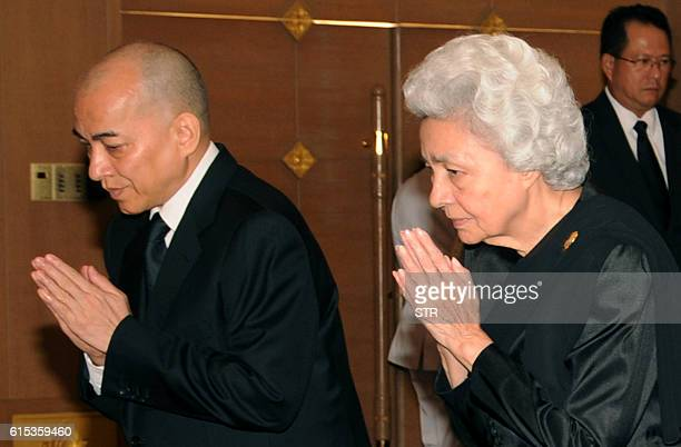 Cambodia's King Norodom Sihamoni and his mother former queen Monique pay respects in front of a portrait of the late Thai King Bhumibol Adulyadej at...