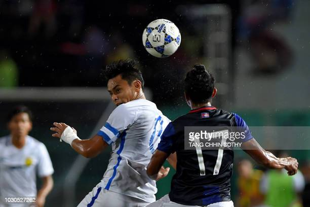 Cambodia's midfielder Chhin Chhuoeun fights for the ball with Malaysia's forward Mohamad Zaquan Adha Abdul Razak during an international friendly...